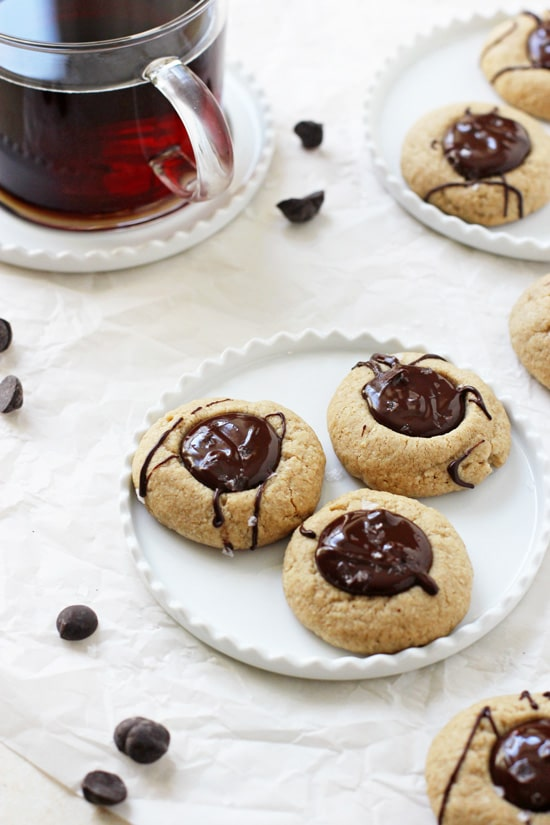 A small plate with three Chocolate Peanut Butter Thumbprint Cookies with more cookies and coffee in the background.