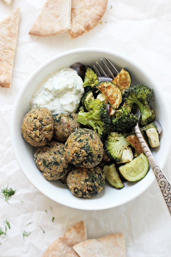 A bowl filled with roasted veggies, Greek Vegetarian Meatballs and tzatziki sauce with a fork.