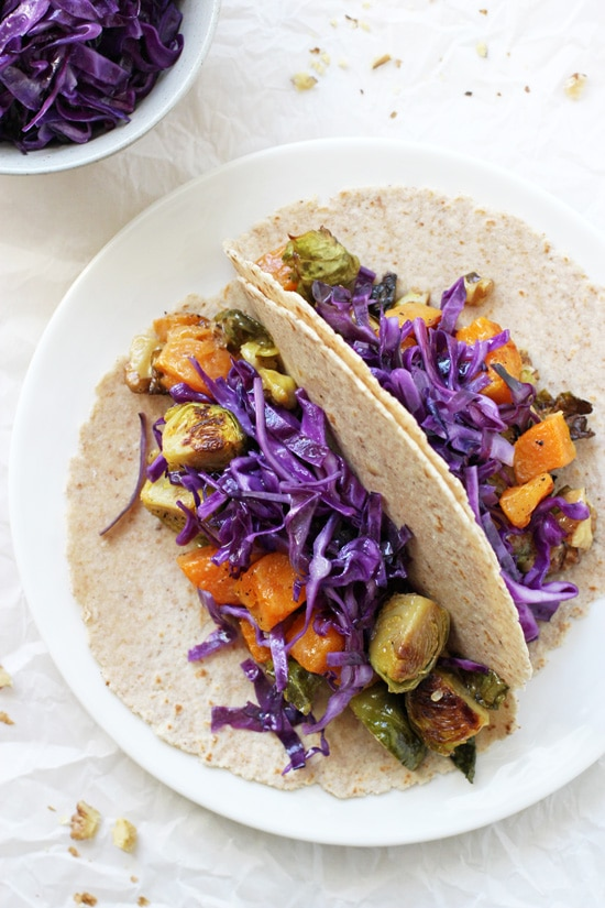 A white plate with two Roasted Winter Vegetable Tacos with a bowl of cabbage to the side.