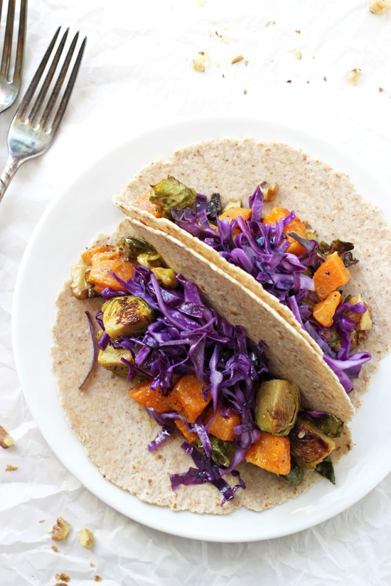 A white plate with two Roasted Winter Vegetable Tacos and two forks to the side.