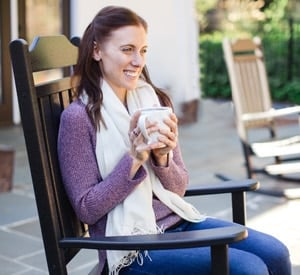 A woman sitting in a rocking chair holding coffee.