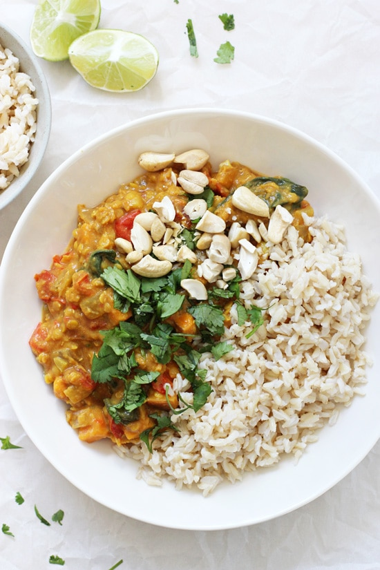 A white bowl filled with Slow Cooker Sweet Potato Spinach Curry and brown rice.