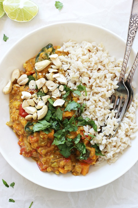 A white bowl with Slow Cooker Sweet Potato Spinach Curry, brown rice and two forks.