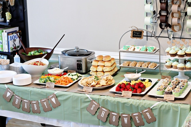 A full buffet spread for a baby shower on a green tablecloth.