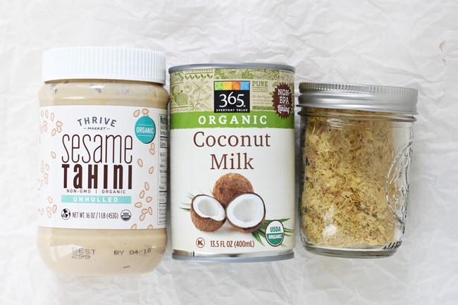 A jar of tahini, canned coconut milk and a jar with nutritional yeast on white parchment paper.