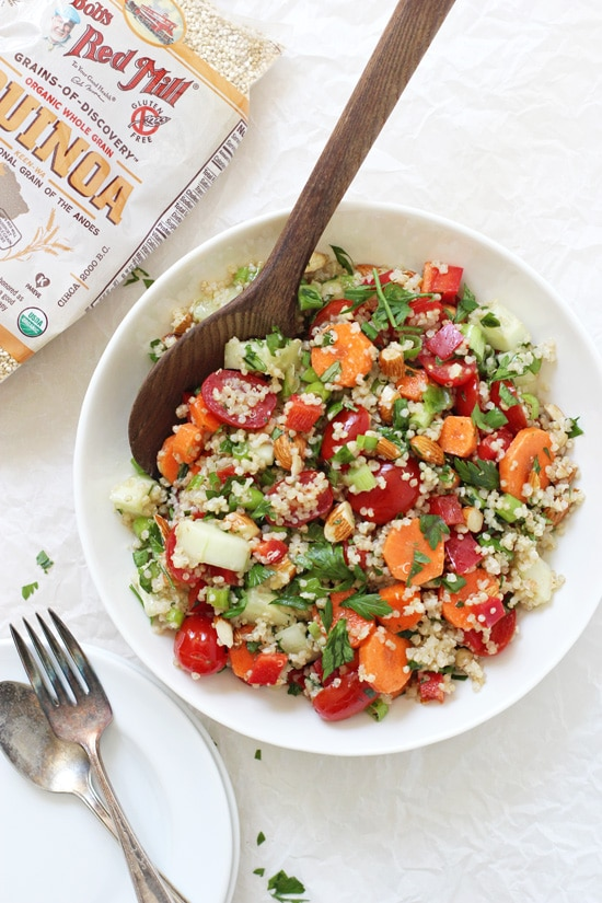 A bowl with Crunchy Summer Veggie Quinoa Salad with plates and a bag of quinoa in the background.