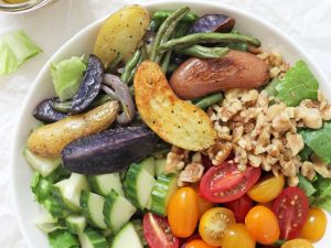 Easy greek salad with roasted vegetables! This healthy dish is packed with fingerling potatoes, green beans, fresh veggies and a flavorful vinaigrette! Serve as a side or as a main topped with a protein of choice!