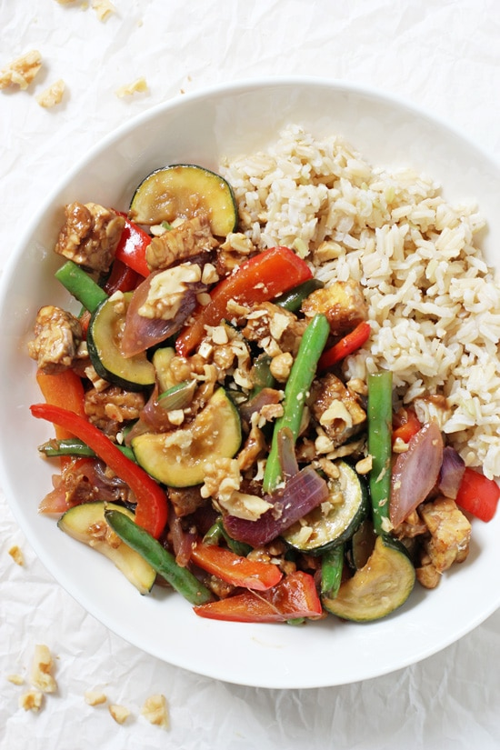 A white bowl filled with Garlic Ginger Summer Veggie Stir-Fry and brown rice.