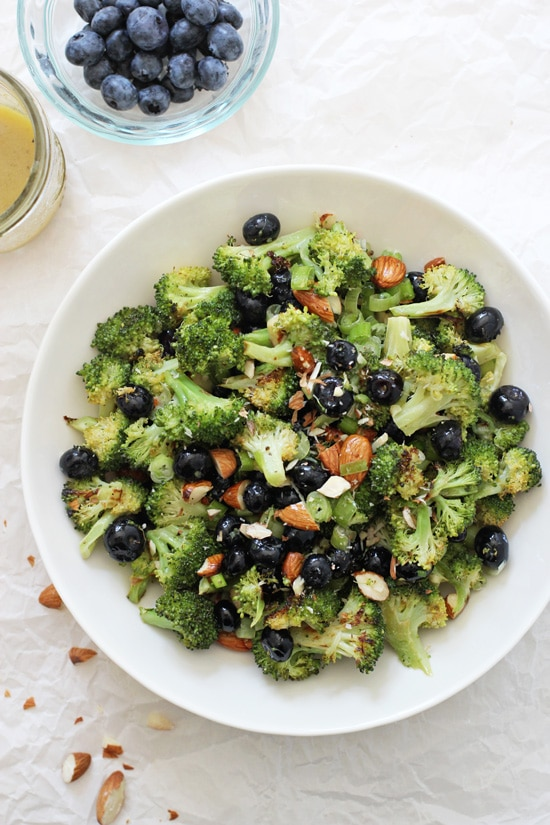 A large white bowl filled with Roasted Broccoli Salad with blueberries and salad dressing to the side.