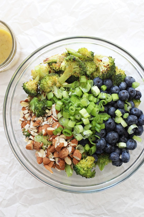 A glass bowl filled with roasted broccoli, blueberries, almonds and green onions.
