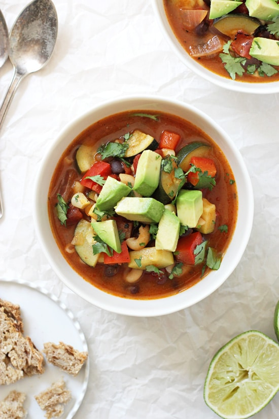 Two bowls of Mexican Minestrone Soup with a plate of bread, two spoons and a lime.