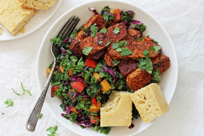 A large white bowl filled with kale salad, BBQ tempeh and cornbread with a fork.