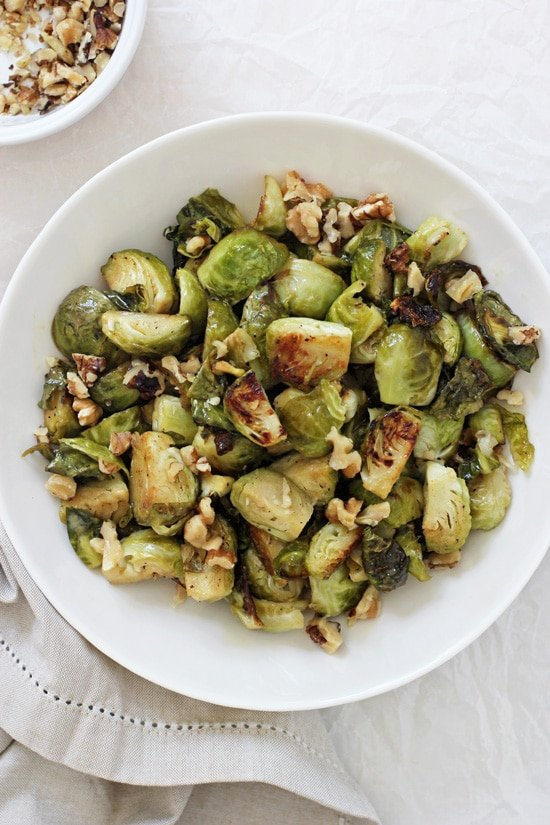 A large white bowl filled with Maple Mustard Roasted Brussels Sprouts and a bowl with walnuts in the background.