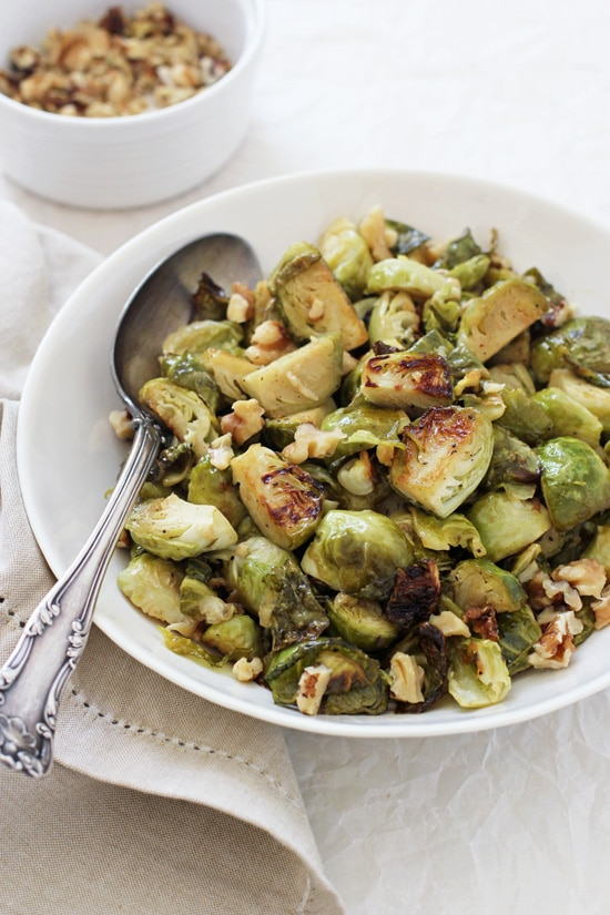 A side angle view of a bowl with Maple Mustard Roasted Brussels Sprouts with a spoon and walnuts in the background.