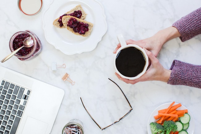 An overhead view of a computer, toast with jam, fresh veggies and hands holding a cup of coffee.