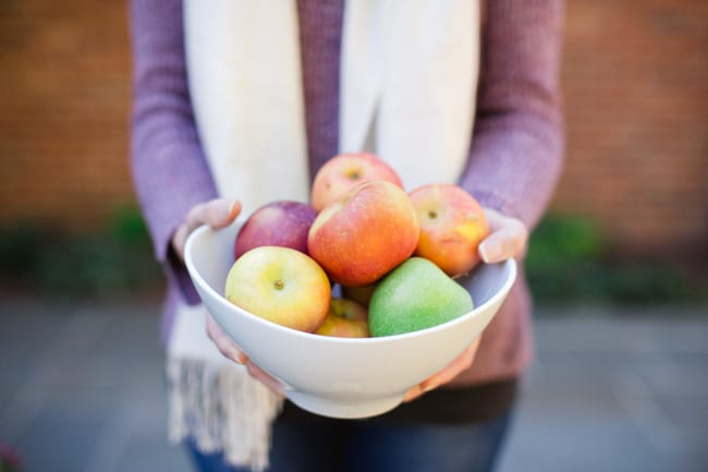 A woman holding a large white bowl filled with colorful apples.