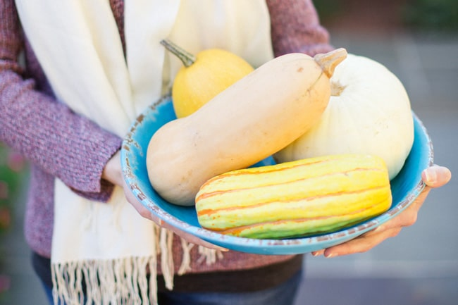 A woman holding a large blue bowl filled with assorted winter squash.