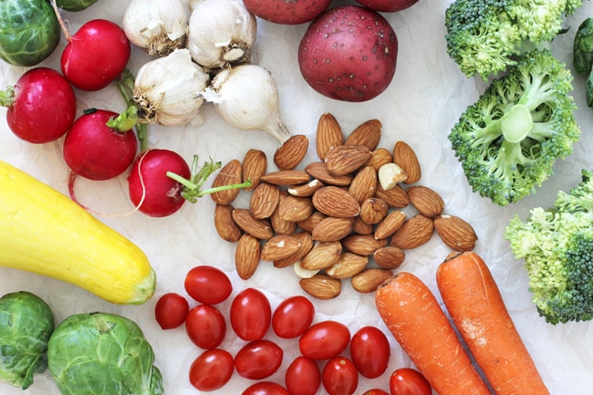 An overhead view of assorted fresh veggies, garlic and whole almonds.
