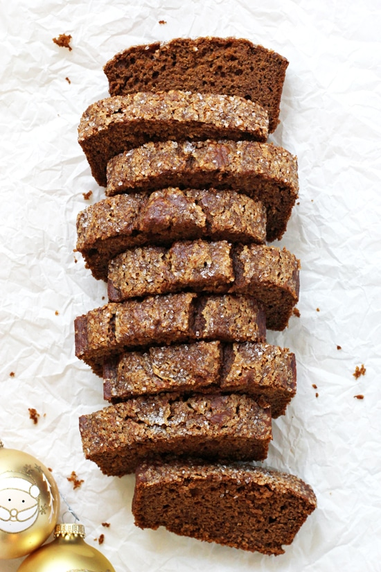 A full loaf of Healthy Spiced Sweet Potato Bread sliced up on parchment paper with Christmas ornaments on the side.