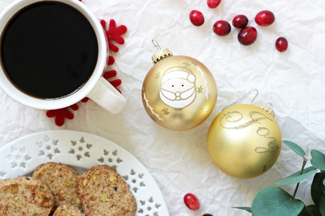 A cup of black coffee, a plate of cookies, two Christmas ornaments and some fresh cranberries scattered around.