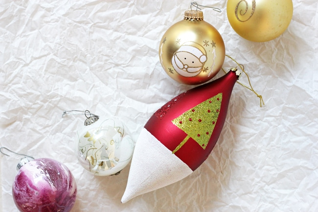 Five different Christmas ornaments on crinkled white parchment paper.