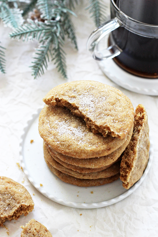 A stack of six Chewy Cardamom Spice Cookies on a white plate with a cup of black coffee in the background.