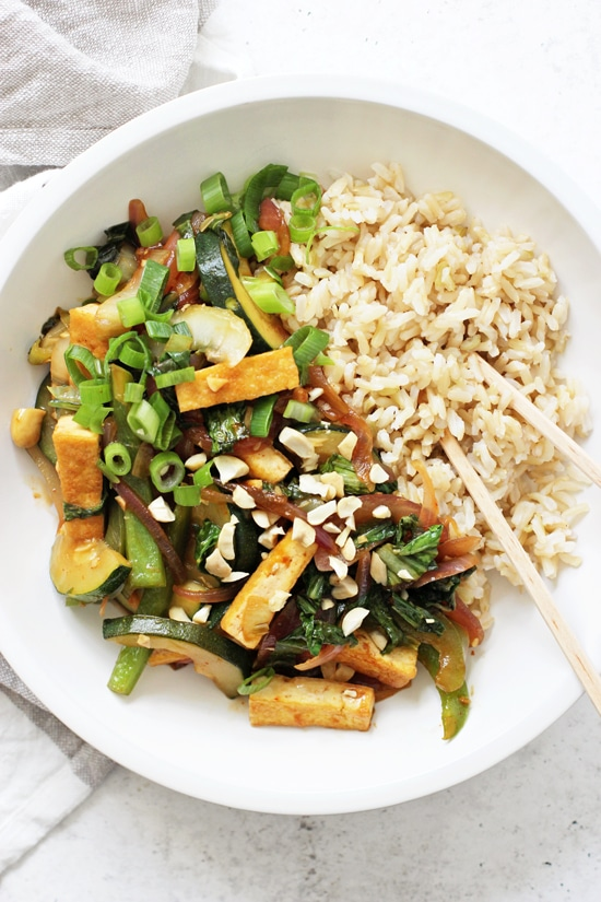 An overhead photo of Kung Pao Tofu with brown rice, cashews and chopsticks.