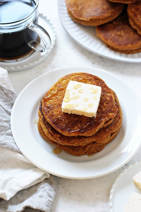 A plate with three Vegan Sweet Potato Pancakes with a pat of butter and coffee in the background.
