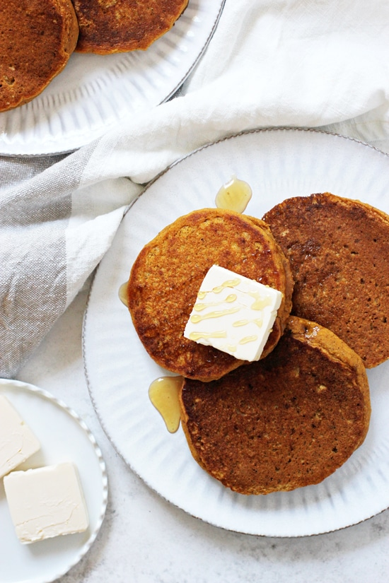 Two white plates with Vegan Sweet Potato Pancakes and pats of butter plus maple syrup.