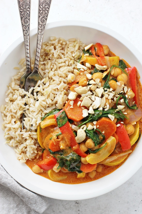 An overhead photo of Coconut Chickpea Curry with brown rice, cashews and two forks.