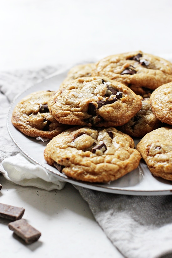 A white plate piled with Mint Chocolate Chip Cookies with a grey napkin and chocolate chunks in the background.