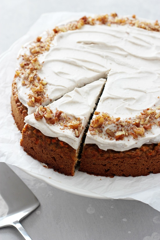 Dairy Free Carrot Cake on a white cake stand with one slice cut out.