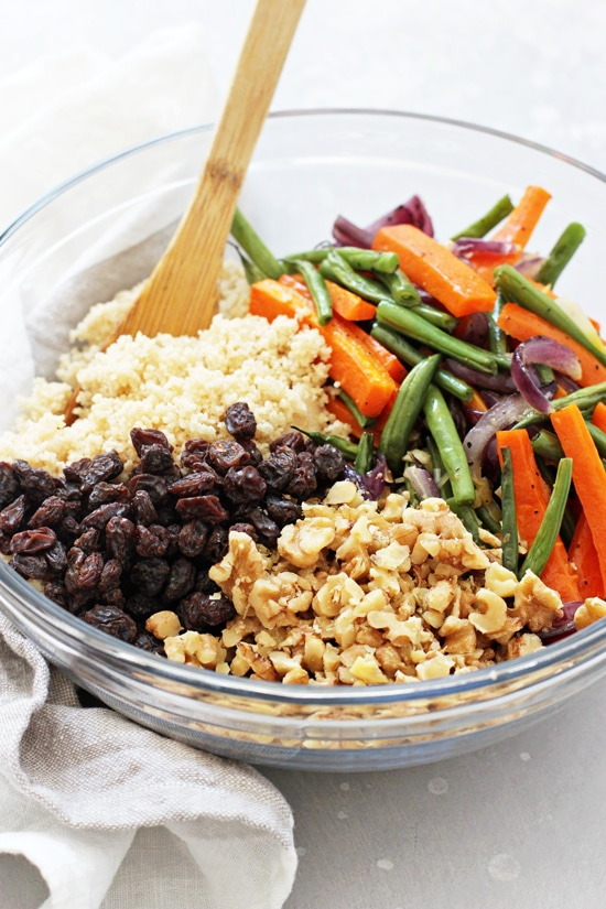 A large glass bowl filled with couscous, roasted veggies, walnuts and raisins.