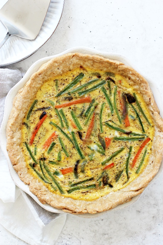 A whole Veggie Packed Dairy Free Quiche on a white background with plates and a cake server on the side.