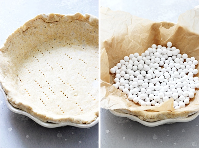 A dairy free pie crust in a pie dish, and then topped with parchment paper and pie weights.