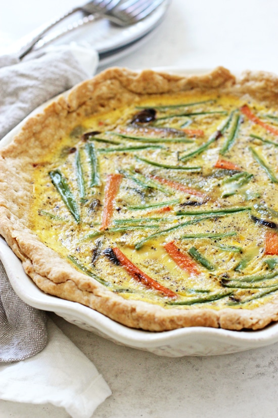 A whole Veggie Packed Dairy Free Quiche on a white background with a white napkin.