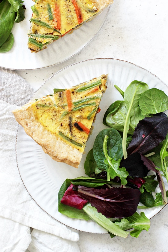 Two individual slices of Veggie Packed Dairy Free Quiche on plates with side salads.