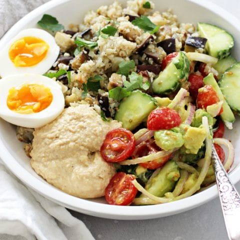 Fast, fresh and simple, these mediterranean hummus bowls are a perfect weeknight meal! With cauliflower rice, fresh tomatoes + cucumber, creamy hummus and soft boiled eggs! They're healthy and excellent for meal prep! Gluten and dairy free!