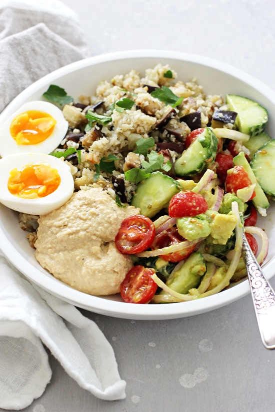A white dish filled with Mediterranean Hummus Bowls with a fork in the bowl.