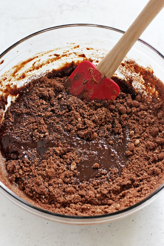 A glass mixing bowl with partially stirred together brownie batter.