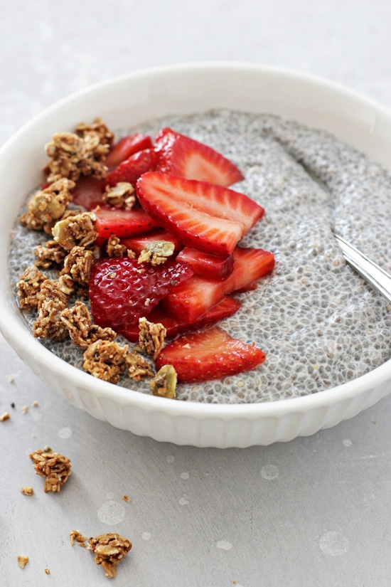 A white bowl filled with Berry Chia Pudding and a sprinkle of granola.