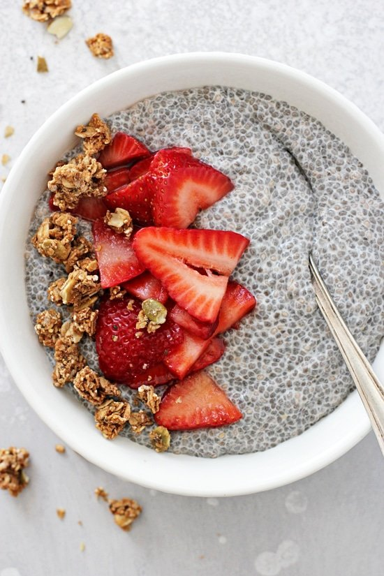 A white bowl filled with Chia Strawberry Pudding with a spoon in the dish.
