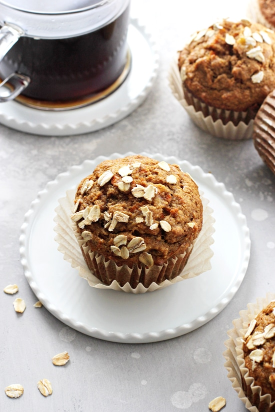A Healthy Banana Carrot Muffin on a white plate with more to the side.