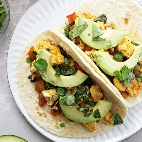 These 25 minute, freezer friendly healthy breakfast tacos are a perfect easy breakfast or dinner! Filled with red onion, bell pepper, scrambled eggs and plenty of spices, plus avocado and salsa for serving. Vegetarian, gluten-free and dairy-free.