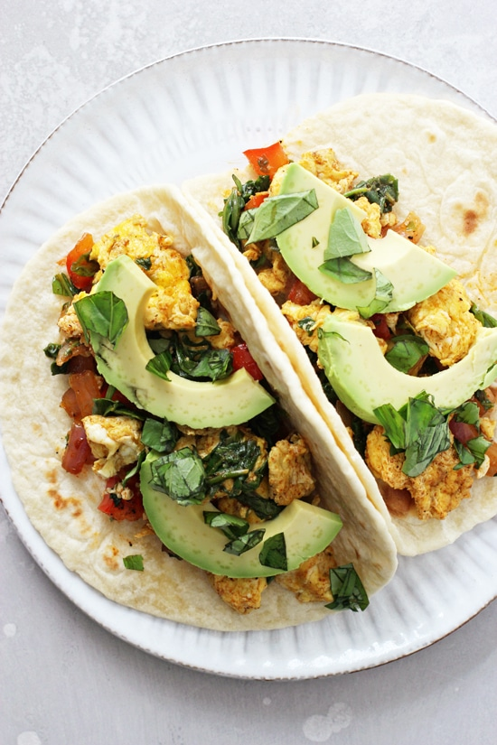 Two Vegetarian Breakfast Tacos on a white plate.