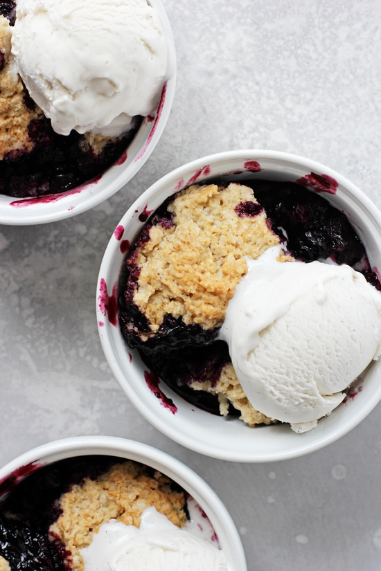 Three ramekins of Vegan Berry Cobbler topped with ice cream.