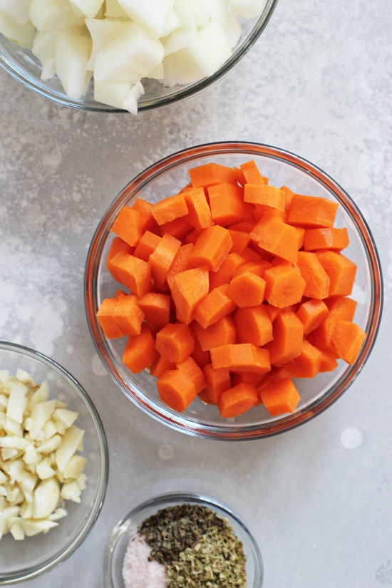 Small glass bowls filled with chopped carrots, onion and garlic.