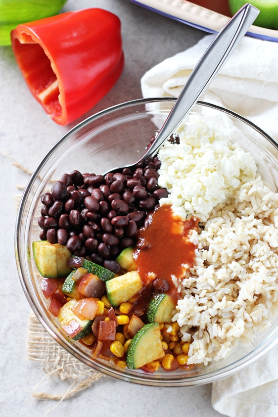 A glass mixing bowl filled with brown rice, black beans, veggies and enchilada sauce.