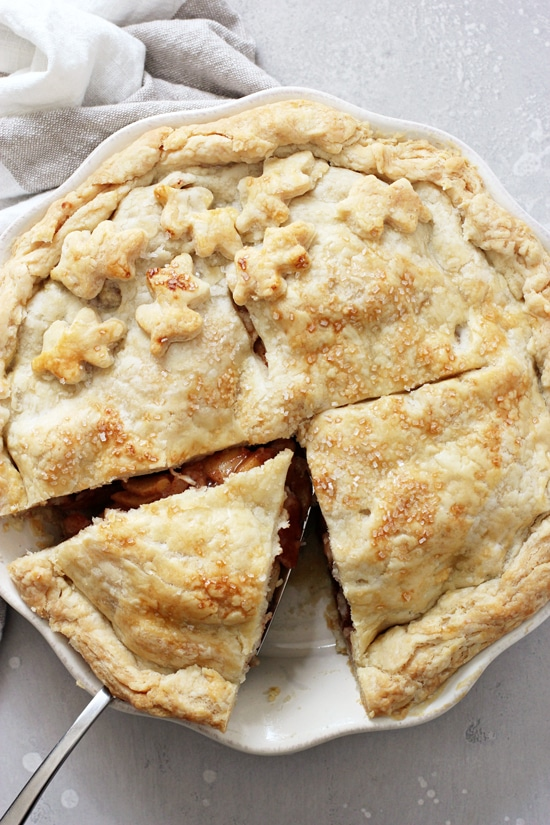 A baked Vegan Apple Pie with one slice cut out.