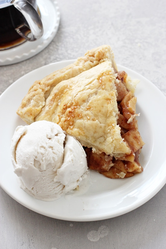 A slice of Dairy Free Apple Pie on a plate with a scoop of ice cream.